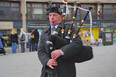 Scottish Bagpiper, Edinburg, Scotland. Scottish Bagpiper in uniform, in plaid and kilt with the Bagpipe, Princess Street, Edinburgh, Scotland, EDINBURGH- 3/17/ royalty free stock image