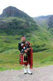 Scottish bagpipes. Scottish piper dressed in kilt in Highland Royalty Free Stock Photos
