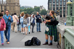 Scottish busker. London, England, Circa July 2014. Scotsman playing the bagpipes to earn some money busking. situated on Westminster Bridge Royalty Free Stock Photography