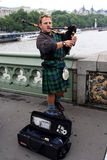 Scottish busker. London, England, Circa July 2014. Scotsman playing the bagpipes to earn some money busking. situated on Westminster Bridge Royalty Free Stock Images