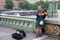 Scottish busker. London, England, Circa July 2014. Scotsman playing the bagpipes to earn some money busking. situated on Westminster Bridge Stock Photography
