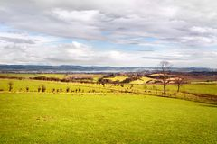 Pastures under picturesque sky in West Lothian, Scotland. Scottish countryside, pastures and farmland under picturesque sky, in West Lothian Stock Image