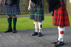 Scottish culture: three kilts. Three Scots bagpipe players wearing different kilts royalty free stock image