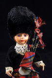 Scottish doll. Dressed in a kilt with bagpipes on black background Stock Photography