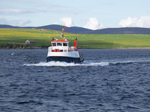 Scottish ferry boat. Small ferry entering a harbor in the Orkney Islands of northern Scotland stock photography