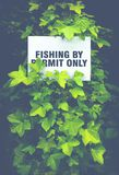 Scottish Fishing By Permit Only Sign. Fishing By Permit Only Sign Hidden In The Foliage By A Scottish River stock image