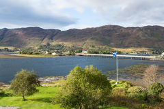 Scottish flag near Eilean Donan castle. Scottish flag waving in the wind near Eilean Donan castle in Dornie, between Skye and the Highlands of Scotland. The Royalty Free Stock Images