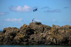 Scottish Flag and Rusting Anchor at a Scottish Harbour. Scottish saltire flag and rusting anchor at Portpatrick harbour in southern Scotland royalty free stock photography