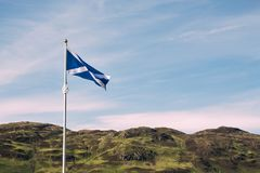 the scottish flag waves in the wind with typical highland scenery in the background stock image