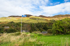 Scottish flag waving in the wind near Eilean Donan castle. Scottish flag waving in a strong wind near Eilean Donan castle in Dornie, between Skye and the Stock Photos