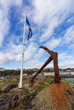 Scottish flag and anchor in Portpatrick harbor in Scotland, United Kingdom. Scottish flag on a white flagpole and rusty boat anchor in Portpatrick harbor on an stock photography