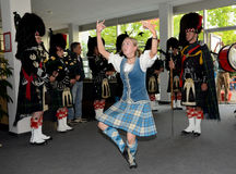 A Scottish folk dancer. Young Scottish folk dancer with band - performance at sales event - Ulm stock image