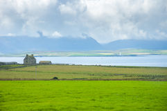 Scottish green landscape, farm and lighthouse in sea bay in back Stock Photography
