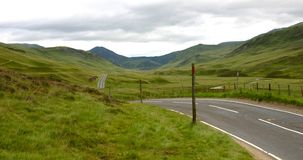Scottish Highlands. Road receding through Scottish Highlands with mountains in background Royalty Free Stock Images