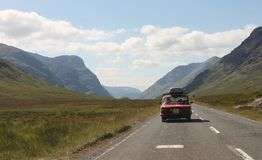 Scottish Highlands landscape in summer - old car on the road in the valley. Stock Photography