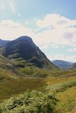 Scottish Highlands landscape in summer - road in the valley. Scottish Highlands landscape in summer with blue sky, white clouds and sunshining. Road in the royalty free stock photos
