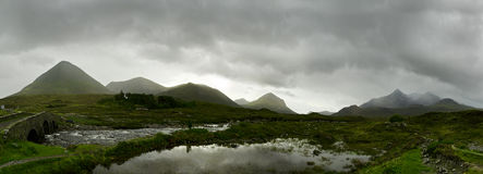Scottish Highlands Panorama. Panorama of the scottish highlands with a river and a lake in front, the mountains are covered in fog and clouds royalty free stock images