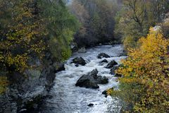 Scottish Highlands river in autumn. Scottish Highlands Clunie waters Braemar. River flowing over rocks in a small cutting with autumn coloured trees stock image