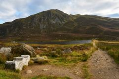 A Scottish hill in Cairngorms National Park. Ben Vrackie, a Scottish cobbler hill in Cairngorms National Park with a wooden carved bench in the foreground Royalty Free Stock Photo