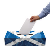 Scottish independence referendum. Ballot box covered in scotlands flag with person casting vote on blank voting slip Royalty Free Stock Photography