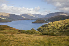Scottish lake in the highlands. Blue lake surrounded by hills with green grassy hills in the foreground and highland hills in the background against partly Stock Photography