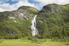 Scottish landscape with forest, mountain and waterfall Royalty Free Stock Images