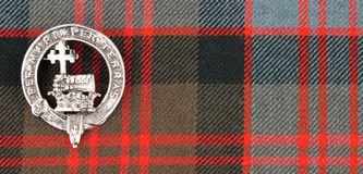 Scottish MacDonald Clan Family Crest On Tartan Fabric Background. Scottish MacDonald clan family crest isolated on tartan fabric background royalty free stock photography