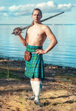 Scottish man with sword near the sea Stock Image