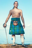Scottish man with sword near the sea. Brave man with sword in scottish costume near the sea Stock Photos