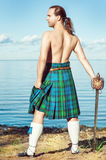 Scottish man with sword near the sea Royalty Free Stock Photo