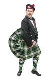 Scottish man in traditional national costume with blowing kilt. Isolated Stock Image