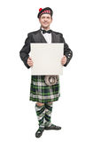 Scottish man in traditional national costume with empty banner Stock Images