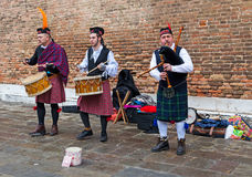 Scottish Musical Band. Venice, Italy-February 18, 2012: Traditional Scottish musical band performing in front of a brick wall in a square in Venice during the Royalty Free Stock Photo