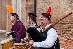 Scottish Musical Band. Venice, Italy-February 19, 2012: Traditional Scottish musical band performing in front of a brick wall in a square in Venice during the Royalty Free Stock Photo