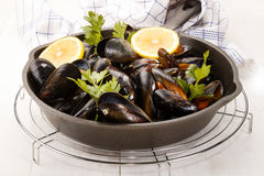 Scottish mussels with parsley and lemon in a cast iron pan Royalty Free Stock Photography