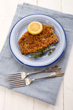 Scottish with oatmeal coated kipper with thyme and slice lemon. An a blue plate Royalty Free Stock Image