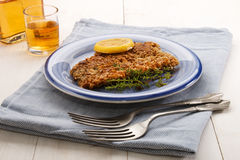 Scottish with oatmeal coated kipper with thyme and slice lemon. An a blue plate Stock Images