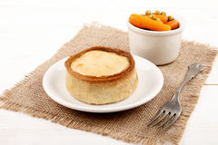 Scottish pie on a plate and a bowl with pea and carrot Royalty Free Stock Images