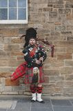 Scottish piper man dressing in Scottish traditional tartan kilt playing a bagpiper at Royal Mile in Edinburgh, Scotland, UK. Edinburgh, Scotland - April 2018: A stock photography