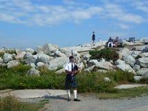 Scottish Piper Playing Bagpipes an Peggy-` s Bucht, Nova Scotia lizenzfreies stockfoto