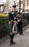 SCOTTISH PIPER PLAYING THE BAGPIPES IN THE STREETS OF EDINBURGH. A man in a traditional scottish kilt playing on bagpipes in Edinburgh. Bagpipes were alluded to Royalty Free Stock Photography