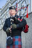 Scottish piper playing music with bagpipe, Edinburgh, Scotland. Edinburgh, Scotland - March 4, 2010: Scottish piper playing music with bagpipe, Edinburgh Royalty Free Stock Images