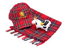 Scottish Red tartan cap, tartan scarves and highland cattle Stock Images
