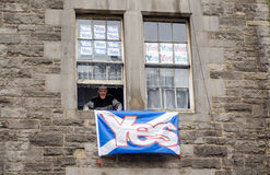 Scottish Referendum Yes Supporter. EDINBURGH, SCOTLAND - SEPTEMBER 11, 2014: An elderly man smiling from the window of his Edinburgh flat which is covered in Yes Stock Photos