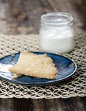 Scottish Shortbread Cookies. A blue plate with a Scottish Shortbread Cookie and a mason jar glass of milk in the background on a rustic wood table and lace Royalty Free Stock Images