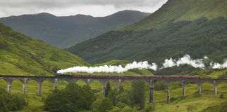 Scottish steam train passing a classic bridge Stock Photo