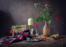 Scottish Still Life. Thistle flowers in a clay vase, a candle in a candlestick, a glass of whiskey on a silver platter, scarves with the Scottish cell package stock photo