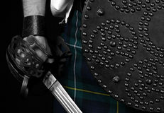 Scottish Sword & Targe. Highlanders basket hilt sword and targe (round studded shield) against Black Watch tartan kilt Stock Image