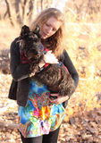 Scottish Terrier Looking While Being Held by Woman. Scottish Terrier dog being held by attractive blond woman Royalty Free Stock Images