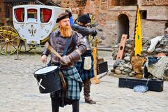 A Scottish warrior, soldier, musician beats the drum on the square of a medieval old castle. Nesvizh, Belarus, October 12, 2018 royalty free stock photo